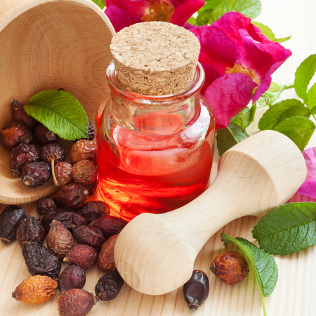 essential oil in glass bottle, dried rose-hip berries in wooden mortar and rose hip flowers on table