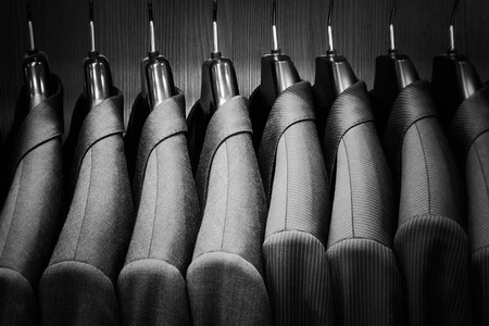 Row of men suit jackets. Black and white image.