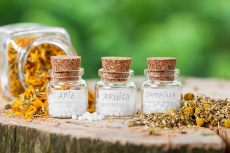 Three bottles of homeopathy globules and healthy herbs.