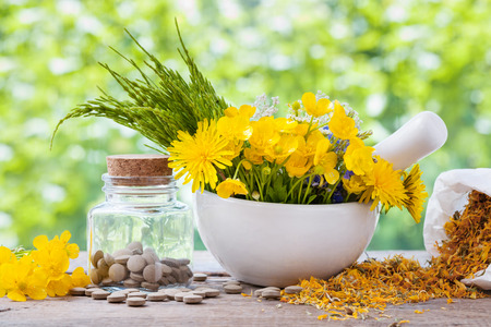 Healing herbs in mortar and bottle of pills on rustic table, herbal medicine.