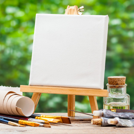 A blank canvas on easel, artistic paintbrushes, tubes of oil paint and bottle of flaxseed oil.
