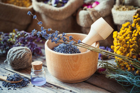 Healing herbs in hessian bags, wooden mortar with lavender flowers, bottles with tincture, herbal medicine. Selective focus.