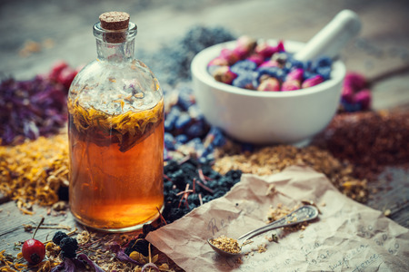 Photo pour Tincture bottle, mortar of healing herbs and paper of recipes on table. Herbal medicine. - image libre de droit