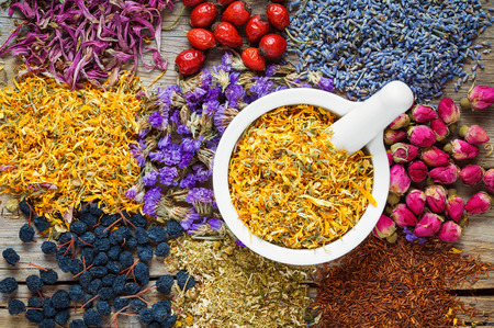 Photo for Mortar of dry marigold flowers, healthy herbs, herbal tea assortment and berries on old wooden table. Herbal medicine. - Royalty Free Image