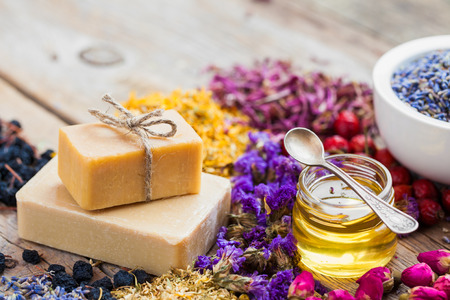 Photo pour Bars of homemade soaps, honey or oil, heaps of healing herbs and mortar of lavender. Selective focus. - image libre de droit