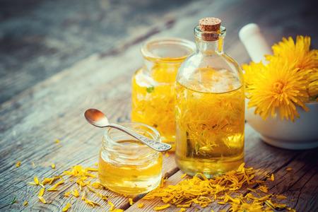 Foto de Dandelion tincture or oil bottles, mortar and honey on table. Herbal medicine. - Imagen libre de derechos
