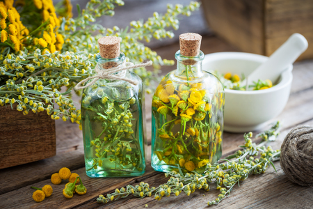 Photo pour Tincture bottles of tansy and tarragon healthy herbs, absinthe healing herbs in wooden box and in mortar. Herbal medicine. - image libre de droit