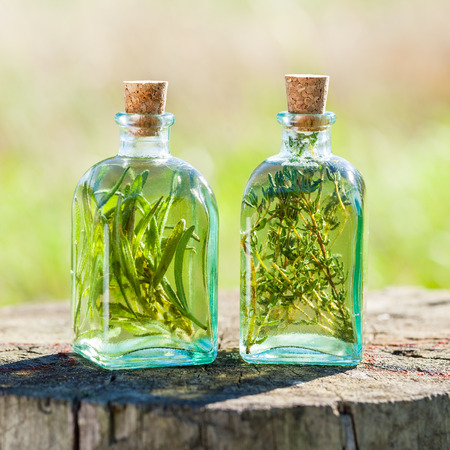 Bottles of thyme and rosemary essential oil or infusion outdoors, herbal medicine.