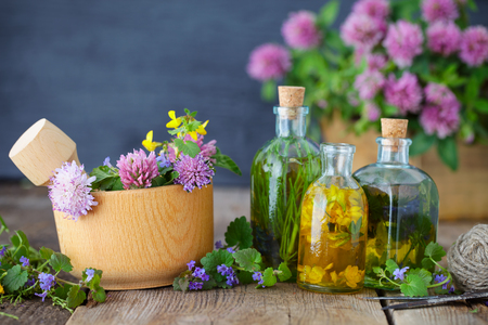 Bottles of tincture or infusion of healthy herbs, healing herbs and wooden mortar of flowers on rustic table. Herbal medicine.