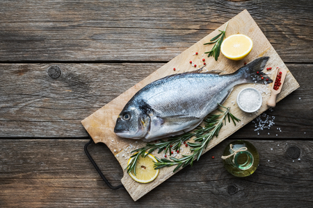 Photo pour Fresh dorado fish with lemon slices,  sea salt and rosemary twigs on wooden cutting board. Top view. Copy space for text. - image libre de droit