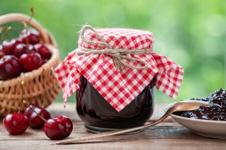 Photo pour Jar of cherries jam, basket of cherries, saucer and spoon on table outdoors. - image libre de droit
