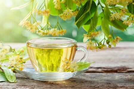 Photo pour Glass cup of healthy tea with linden tree flowers on wooden board, lime tree flowers. - image libre de droit