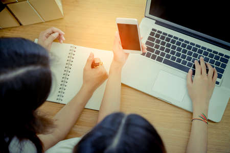 Young asian girl together teamwork freelancer business owner working at home office with laptop, note, mobile, packaging delivery online market on purchase checking orders to customer, Top view