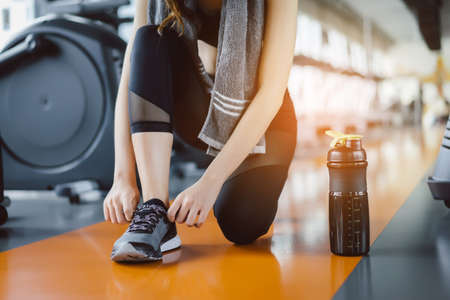 Foto de Young girl asian knelt down to do up his shoelaces with protein shake at fitness gym after running exercise workout for cardio and muscle building. - Imagen libre de derechos