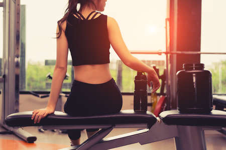 Foto de Woman exercise workout in gym fitness breaking relax holding protein shake bottle after training sport with dumbbell and healthy lifestyle bodybuilding. - Imagen libre de derechos