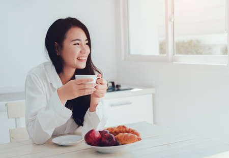 Foto de Asian woman drinking coffee in the morning and eating bread,apple fruit healthy food breakfast meal in kitchen room fresh start the day at home healthy lifestyle concept - Imagen libre de derechos