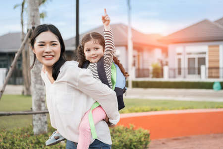 Photo pour Mother get a daughter pupil from school after study school back to home with schoolbag family lifestyle. - image libre de droit