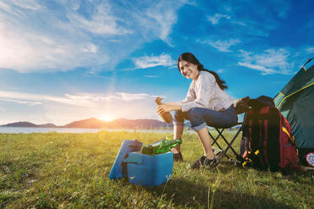 Foto de Asian woman camping and backpack travel sitting relax alone with drinks beer,water for refreshing active at morning having happy lifestyle nature mountain in forest. - Imagen libre de derechos