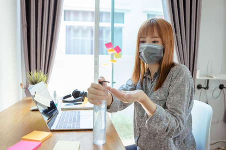 Foto de Asian woman wearing mask pump hand gel alcohol cleaning sanitizer working from home and listening music with headphone prevent the spread of coronavirus quarantine workplace with protective. - Imagen libre de derechos
