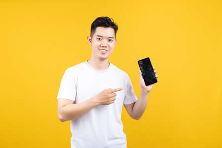 Photo pour Attractive portrait happy young asian man showing mobile phone smiling at camera with copy space wearing white t-shirt on yellow background isolated studio shot. - image libre de droit