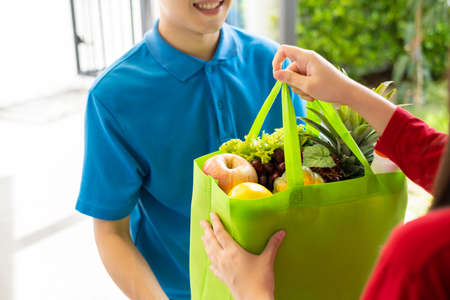 Photo pour Food Deliver Asian man in blue uniform give fruit and vegetable to receiver customer front house, fast express grocery service when crisis coronavirus, covid19 new normal lifestyle concept. - image libre de droit