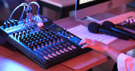 Photo for Close up of asian hand producer working at mixing panel in the boutique recording studio. Modern music record studio control desk of digital audio workstation software. Music production concept. - Royalty Free Image