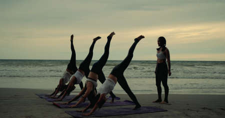 Photo pour Group females yoga practice in class on mat stretching relaxation exercise with pose fitness sport for healthy on the beach and seaside at sunset relax holiday vacation time in summer. - image libre de droit