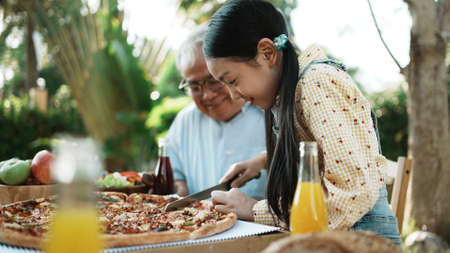 Photo pour Happy asian grandchild take a bite pizza, Multi generation family enjoying meal with grandpa. They having outdoor party eating food at backyard home, lifestyle family concept party at summer garden. - image libre de droit