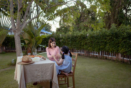 Photo pour Happy asian family mother and daughter dining and tasting dinner party enjoying meal together. People having outdoor eating food at backyard home in garden. - image libre de droit