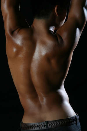 Back of tanned young man with black background