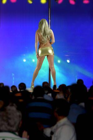 female stripper wearing gold dress dancing in gentlemans club.
