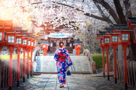 Foto de Back view of asia woman with kimono and Japanese umbrella against sakura flower background - Imagen libre de derechos