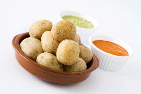 Foto de Canarian potatoes (boiled potatoes) With Mojo sauce isolated on white background - Imagen libre de derechos