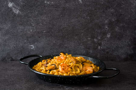 Foto de Traditional Spanish fideua. Noodle paella on black stone. Copyspace - Imagen libre de derechos