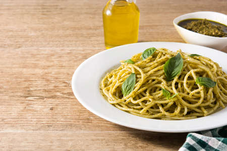 Foto de Spaghetti pasta with pesto sauce on wooden table. Copyspace - Imagen libre de derechos