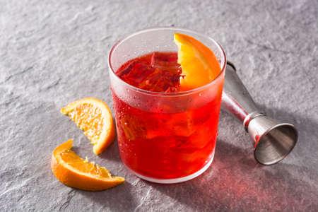 Foto de Negroni cocktail with piece of orange in glass on gray background. - Imagen libre de derechos