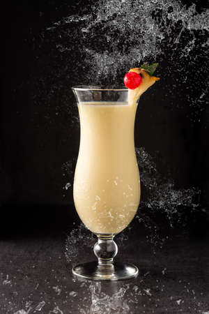 Photo pour Splash of pina colada cocktail decorated with a piece of pineapple and cherry on black background - image libre de droit