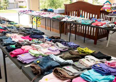 Photo for Tables of clothing and baby goods at suburban garage sale - Royalty Free Image