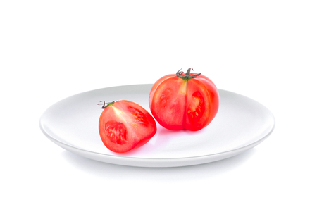 tomato in white plate on white backgroundの写真素材