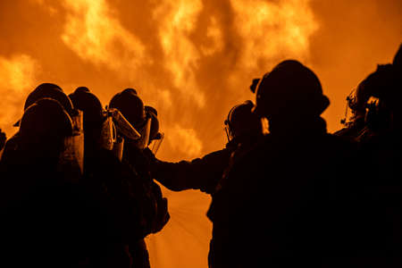 Foto für Firefighters and rescue training. Firefighter spraying high pressure water to fire Burning fire flame background - Lizenzfreies Bild
