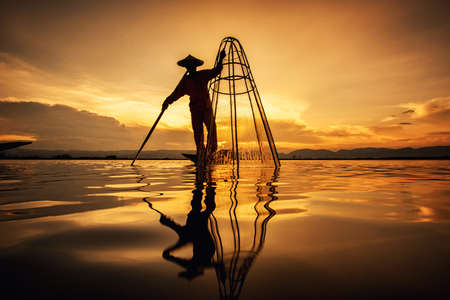 Photo pour Intha Burmese fishermen on boat catching fish traditional at Inle Lake, Shan State, Myanmar - image libre de droit
