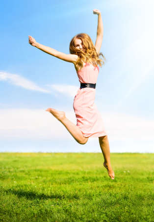 Happy jumping girl on summer field background.