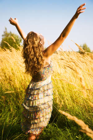 Young woman stretching up in a summer field.