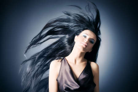 Woman with fluttering hair. On dark background.