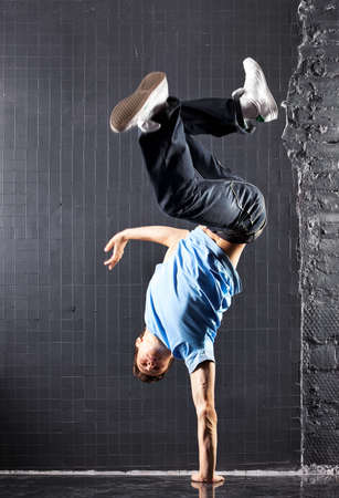 Young man modern dance. On dark wall background.