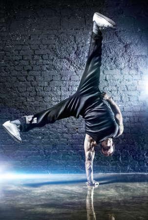 Photo pour Young strong man break dance. On dark wall background. - image libre de droit