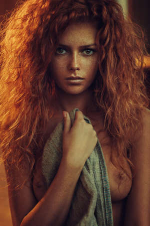 Young woman with red hair indoors nude portrait