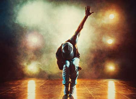 Foto de Young man break dancing in club with lights and smoke. Tattoo on body. - Imagen libre de derechos