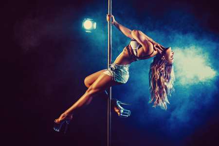 Photo for Young sexy slim woman pole dancing in dark interior with lights and smoke - Royalty Free Image