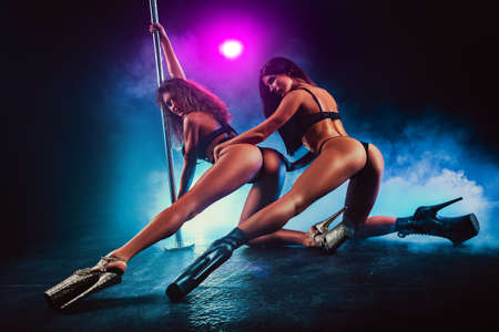 Photo pour Two sexy pole dancing women team in dark interior with smoke and colored lights. - image libre de droit